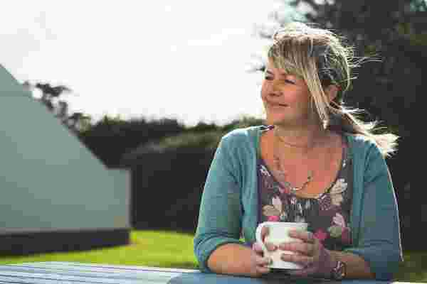 Mel from Highcliffe Holidays sits on a bench with a mug of tea.