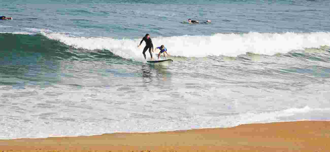 Highcliffe holidaymakers surf at Polzeath beach.