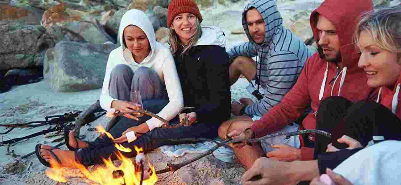 A group wrap up warm and toast marshmallows over a campfire on Polzeath beach near Highcliffe Holidays.