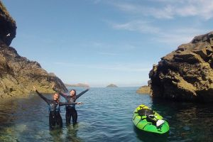 Two girls in wetsuits pose in the sea after kayaking with Cornish Coast Adventures.
