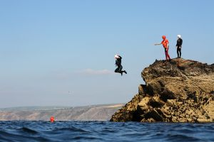 People jump from a rock into the sea while coasteering with Cornish Rock Tors