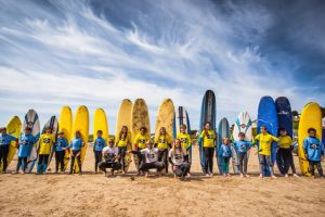 A large group of learner surfers pose with their boards on Polzeath beach, with instructors from Surfs Up Surf School.
