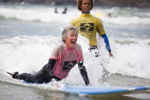 A woman learns to surf with Wavehunters Surf School on Polzeath beach