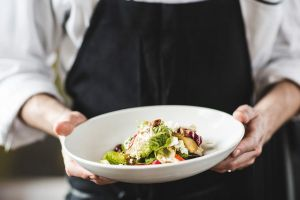 A chef holds a bowl of well-presented food.
