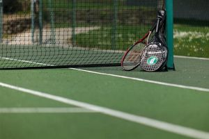 Three rackets are leant against the net at the Highcliffe Holidays on-site tennis courts.
