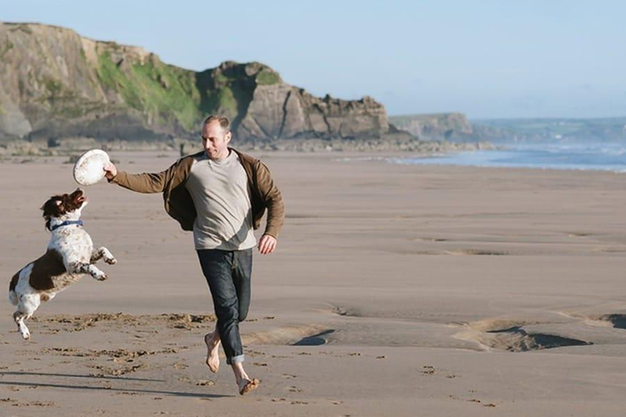 A man plays with his dog at Polzeath beach on the north Cornish coast whilst holidaying with Highcliffe Holidays.